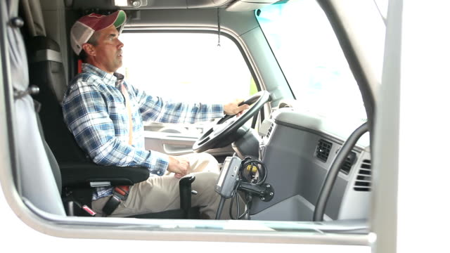 Mature man climbing into cab of semi-truck
