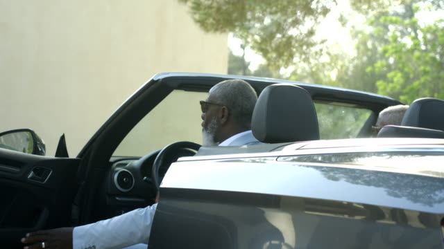 mature man climbs from luxury convertible car - mature men stock videos & royalty-free footage