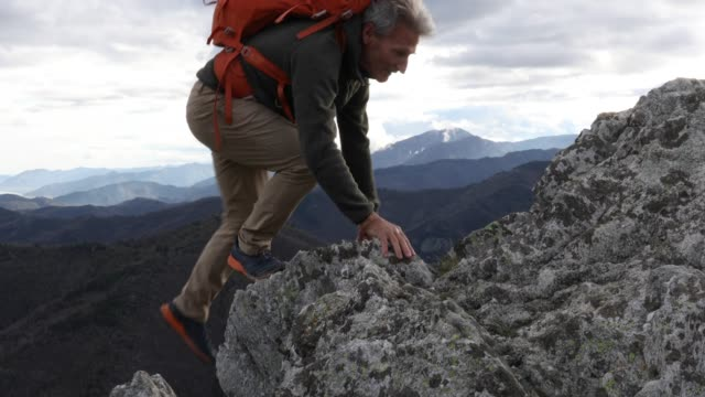 mature man climbs rock ridge, above mountains - rock climbing stock videos & royalty-free footage