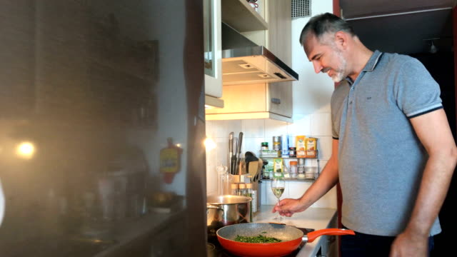 mature man cooking in domestic kitchen - mature men stock videos & royalty-free footage