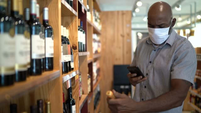 mature man customer buying wine using mobile phone at store - using face mask - modern manhood stock videos & royalty-free footage