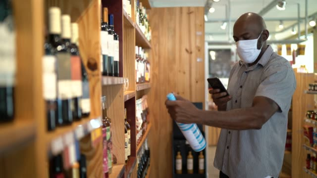 mature man customer buying wine using mobile phone at store - using face mask - photography themes stock videos & royalty-free footage