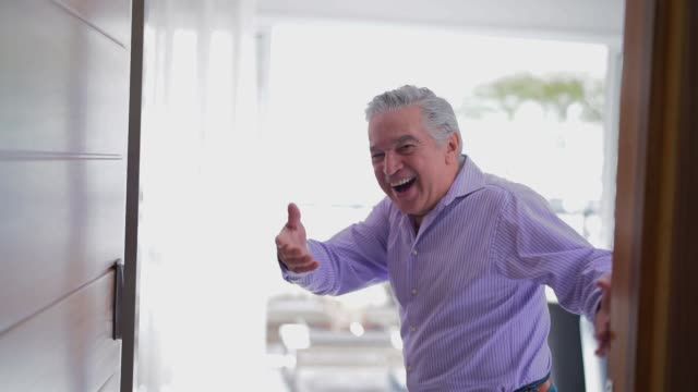Mature Man Dancing and Welcoming Home Opening His Front Door