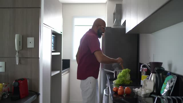 mature man dancing while cooking at home - modern manhood stock videos & royalty-free footage