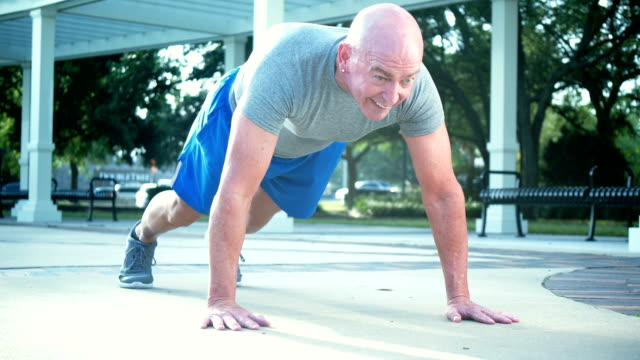 mature man doing exercises in plank position - 50 59 years stock videos & royalty-free footage