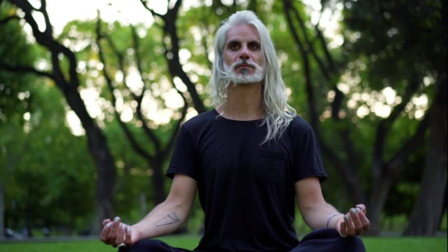 mature man doing yoga in park - buddhism stock videos & royalty-free footage