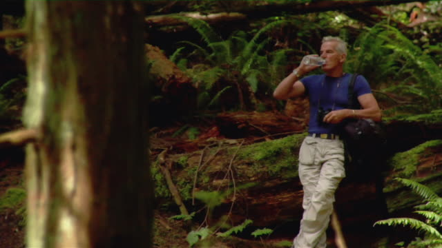 mature man drinking bottled water while birdwatching in forest / looking through binoculars - kelly mason videos stock-videos und b-roll-filmmaterial