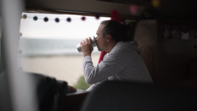 mature man drinking coffee in his camper van on the beach - 日曜日点の映像素材/bロール