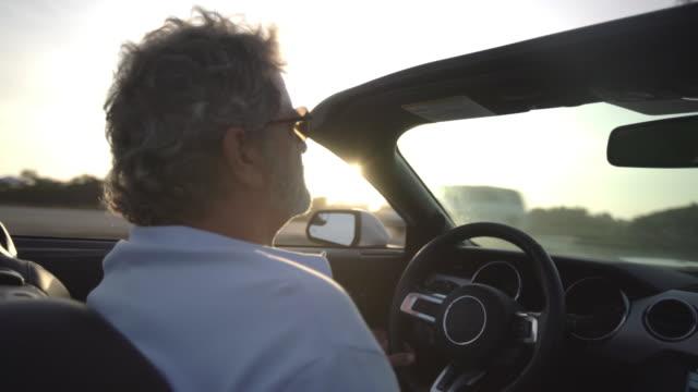 Mature man driving in a convertible along the beach