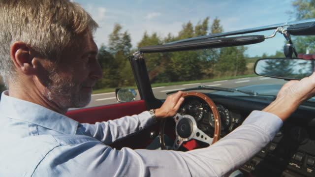 stockvideo's en b-roll-footage met volwassen man rijden vintage auto tijdens winderige dag - ruimte exploratie