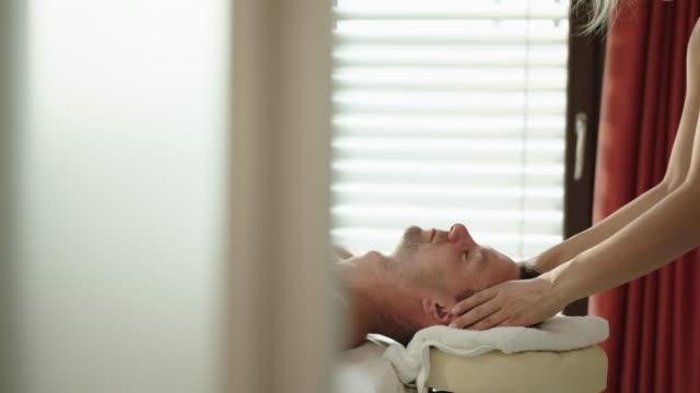 mature man enjoying a head massage at a spa - head massage stock videos and b-roll footage