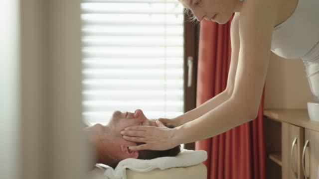 mature man enjoying a head massage at a spa - head massage stock videos & royalty-free footage