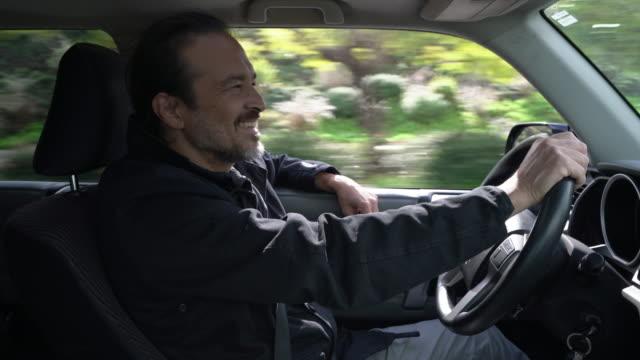 CU Mature man enjoying driving a car