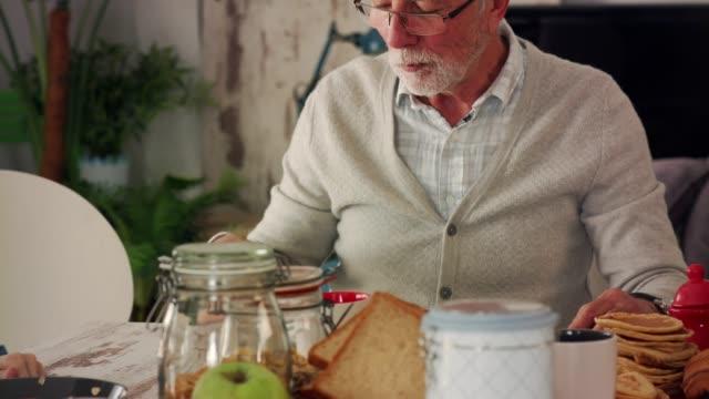 vidéos et rushes de homme mûr appréciant tout en mangeant le petit déjeuner - mâcher
