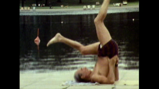 mature man exercises on a mat beside the serpentine lake; 1971 - pilates stock-videos und b-roll-filmmaterial
