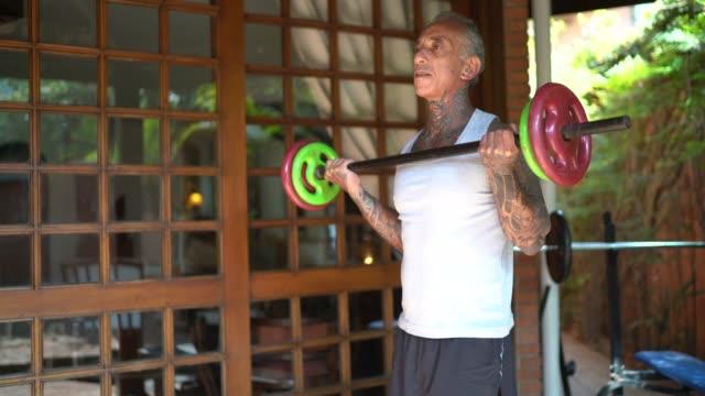vídeos de stock, filmes e b-roll de homem maduro se exercitando em casa - 50 54 anos