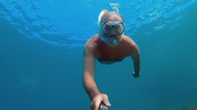 mature man filming himself diving underwater on summer vacations - underwater diving stock videos & royalty-free footage