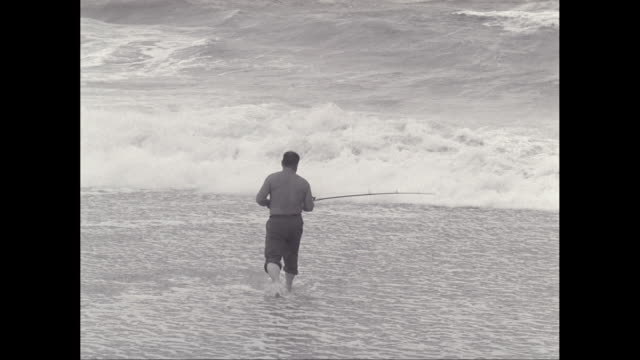 ws ha mature man fishing in sea from beach / united states - brandungsfischen stock-videos und b-roll-filmmaterial