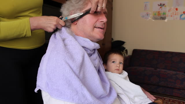 stockvideo's en b-roll-footage met rijpe mens die huiskapsel van zijn vrouw thuis krijgt - in een handdoek gewikkeld