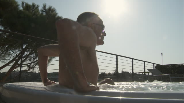 MS LA Mature man getting into outdoor Jacuzzi, Rome, Italy