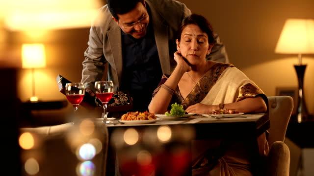vídeos de stock, filmes e b-roll de ms mature man giving surprise gift to his wife in restaurant / delhi, india - mãos cobrindo olhos
