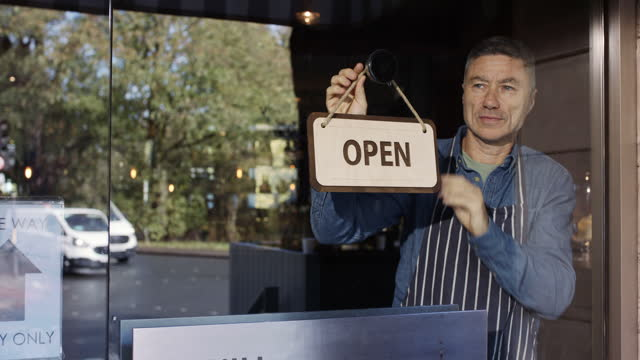 mature man hanging open sign on restaurant window - hanging stock videos & royalty-free footage