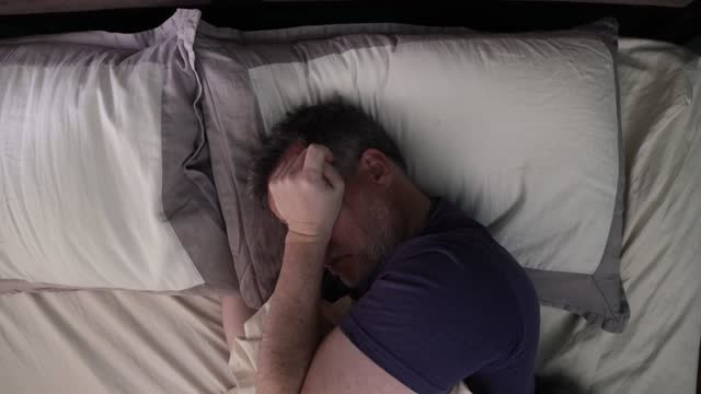 mature man having a hard time waking up and deciding to just go back to sleep - rubbing stock videos & royalty-free footage