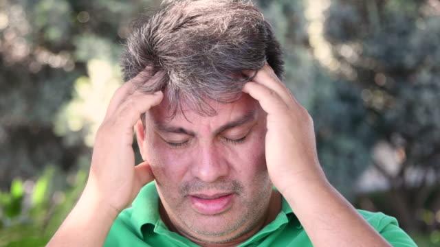 vidéos et rushes de homme mûr ayant un mal de tête - tête composition