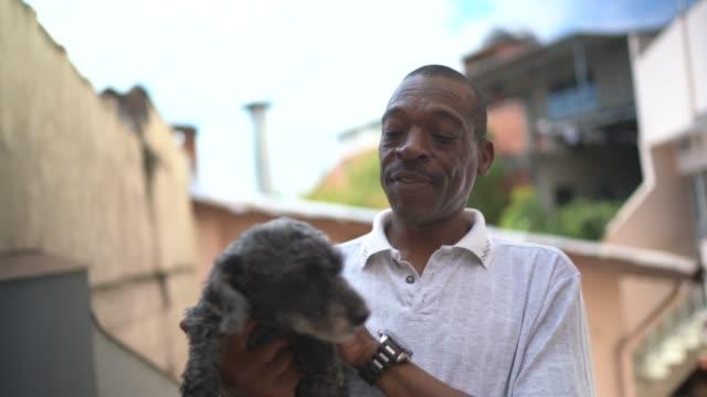 vídeos de stock, filmes e b-roll de homem maduro se divertindo com cachorro em casa - gente comum
