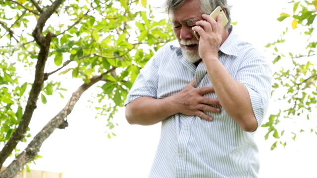 Mature man having heart attack and calling for help