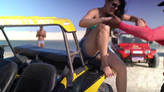 vídeos de stock, filmes e b-roll de homem maduro ajudando jovem a sair de um carro de buggy em dunas de areia - turista