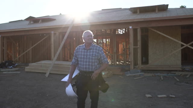 WS Mature man holding a hard hat in front of a home being built