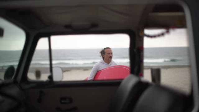 stockvideo's en b-roll-footage met mature man holding a surfboard on the beach - surfbord