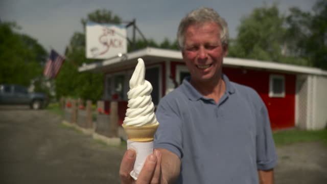 vídeos de stock e filmes b-roll de ms mature man holding ice cone standing in front of americana type roadside snack bar / stowe, vermont, usa - só homens maduros