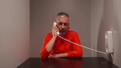 mature man holding telephone and talking during visit in prison - visit stock videos & royalty-free footage