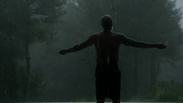mature man holds his arms out in the rain (wide) - atmosphere filter stock-videos und b-roll-filmmaterial