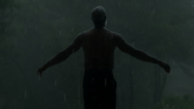 mature man holds his arms out in the rain (medium) - atmosphere filter stock-videos und b-roll-filmmaterial
