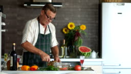 Mature man in glasses prepares a salad in the kitchen. Stir the vegetables in a bowl. Retired with a serious face in the kitchen, seasoning salad