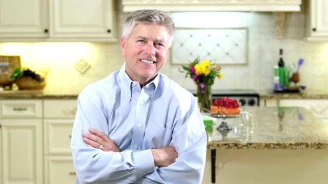 mature man in kitchen, arms crossed, smiling - granite stock videos and b-roll footage