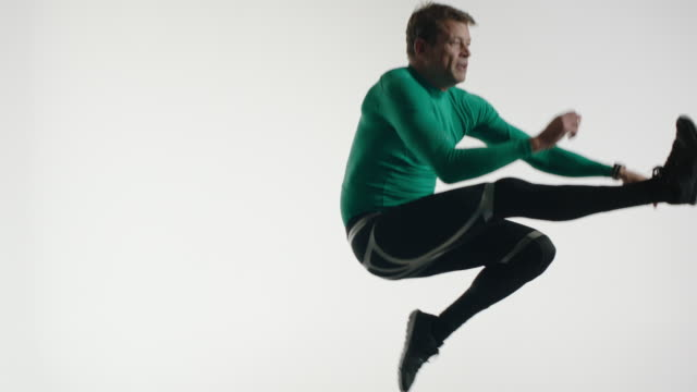 Mature man in running outfit jumping on trampoline
