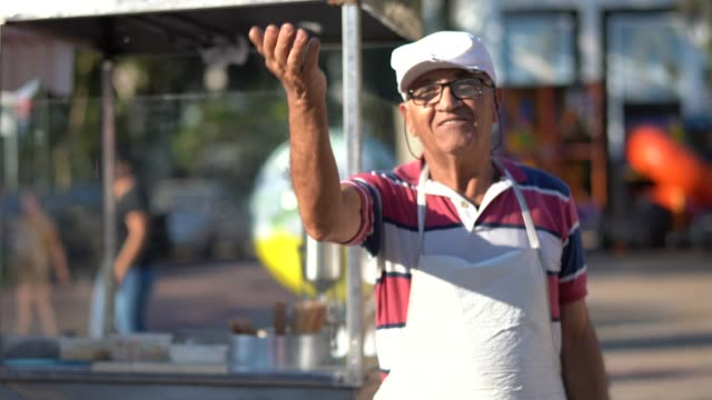 mature man inviting people to come to your churros store - bancarella video stock e b–roll