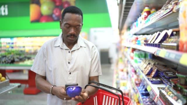 vidéos et rushes de l'homme mûr fait des emplettes dans le supermarché et le code-barres de balayage avec le smartphone - panier courses