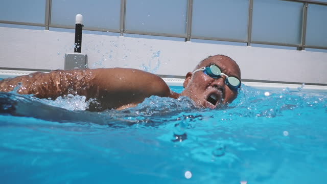 mature man is swimming in the rooftop pool - improvement stock videos & royalty-free footage