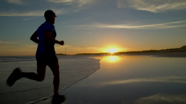 Mature man jogging on a beach at sunset