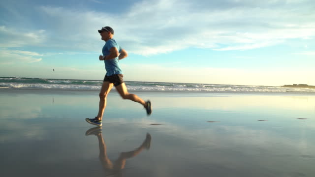 vidéos et rushes de mature man jogging on sandy beach - 45 49 ans