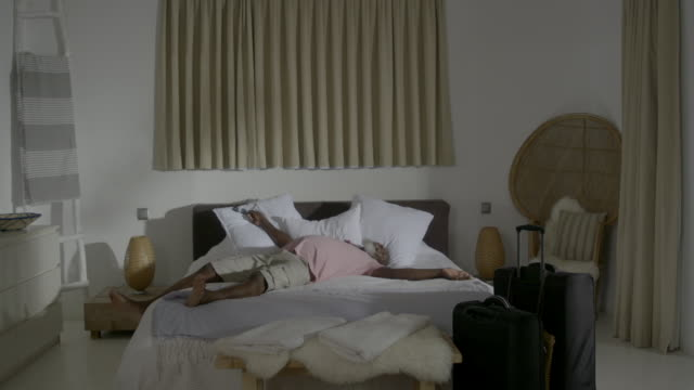 a mature man jumps onto a bed - luxus hotel stock-videos und b-roll-filmmaterial