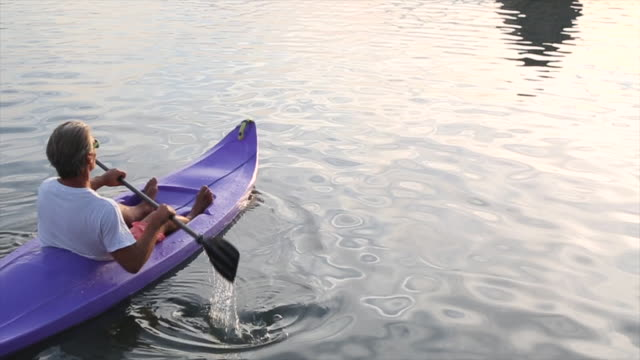 Mature man kayaks out to a partially sunken sarcophagus