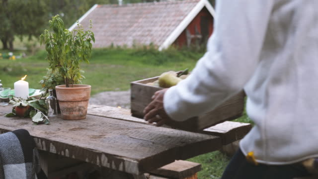 mature man keeping fruit crate on dining table and walking towards friends - tischflächen aufnahme stock-videos und b-roll-filmmaterial