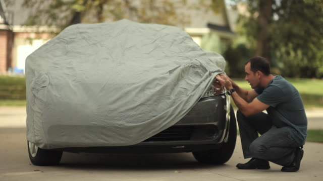 ws mature man lifting car cover to admire his car / neenah, wisconsin, usa  - bedecken stock-videos und b-roll-filmmaterial