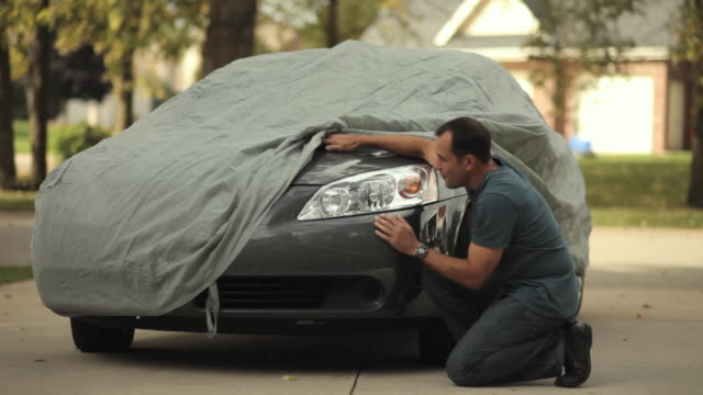 vídeos y material grabado en eventos de stock de ws mature man lifting car cover to admire his car / neenah, wisconsin, usa  - cubrir